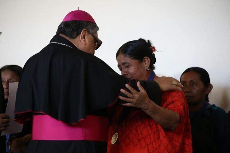 Monseñor Óscar Julio Vian entrega el reconocimiento a una mujer víctima de abusos sexuales durante el conflicto armado interno. (Foto Prensa Libre: Paulo Raquec)