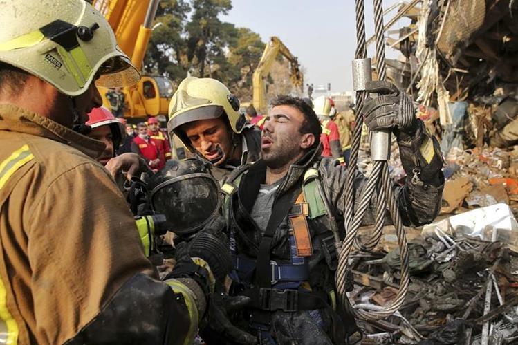 Un socorrista ayuda a uno de sus colegas que trabaja en el lugar del siniestro. (Foto Prensa Libre: AP)