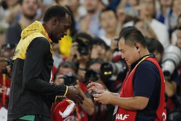 Usain Bolt recibe la pulsera que le regaló Tao Song, tras el incidente de ayer. (Foto Prensa Libre: AFP)