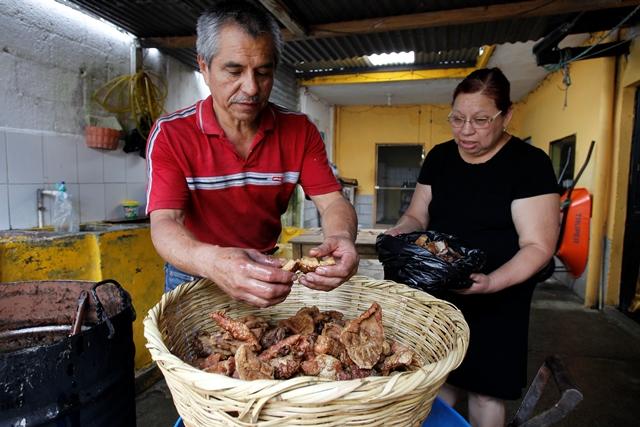 Eligio Castro, junto a su esposa Liliana, muestra la calidad de los chicharrones que prepara. (Foto Prensa Libre: Paulo Raquec)