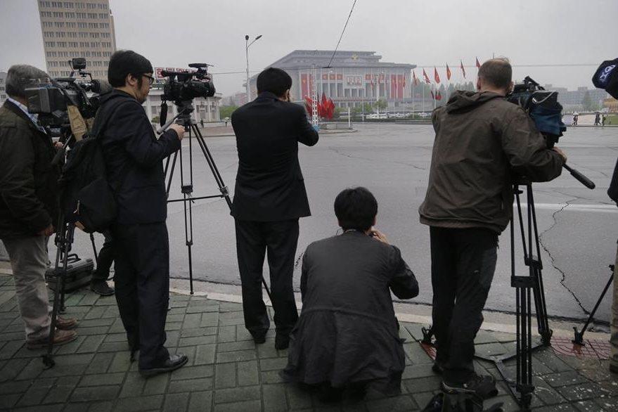 Periodistas extranjeros que cubrieron el congreso norcoreano observan desde lejos la sede del parlamento. (Foto Prensa Libre: AP).