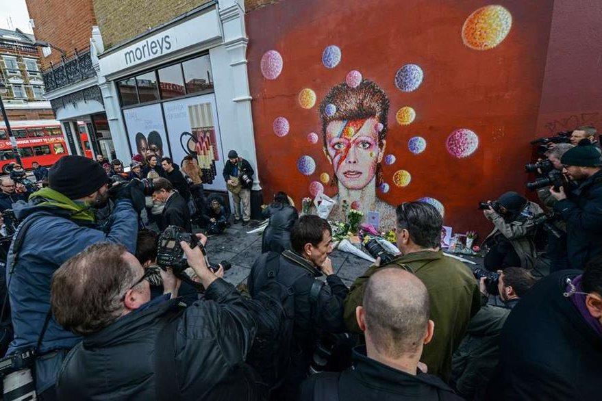 Varios seguidores del cantante británico David Bowie rinden homenaje póstumo en un altar improvisado por sus seguidores en Brixton, Londres. (Foto Prensa Libre: AFP)