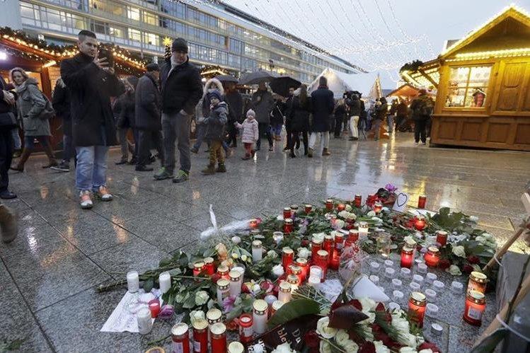 Un mercado navideño en Berlín donde velas, flores y fotografías recuerdan a las víctimas del atentado terrorista del 19 de noviembre último. (Foto Prensa Libre: AP).