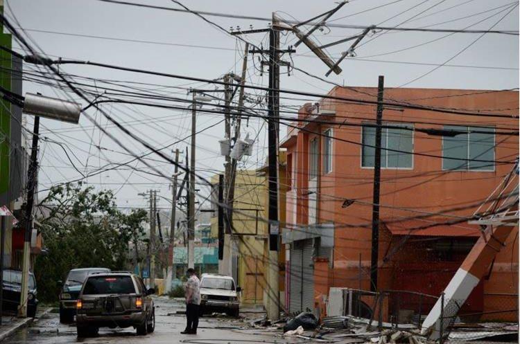Líneas de electricidad destruidas en una colonia de viviendas en Puerto Rico. (Foto Prensa Libre: AP)