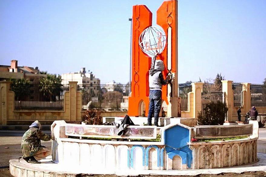 Dos militantes yihadistas pintan un monumento en la plaza central de Raqa. (Foto Prensa Libre: AP).