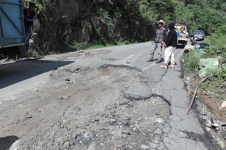 Ante la indiferencia de las autoridades, vecinos de cinco municipios de la cuenca del Lago de Atitlán, Sololá, reparan la carretera. (Foto Prensa Libre: Ángel Julajuj)