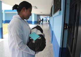 Una enfermera traslada el cuerpo de un niño a la morgue del hospital de Huehuetenango. (Foto Prensa Libre: Mike Castillo).