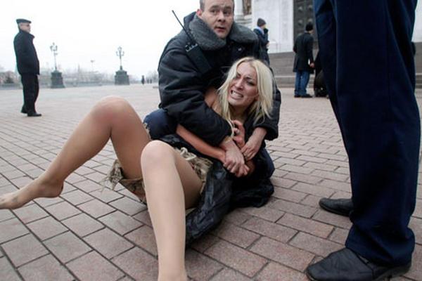 <p>Un guardia de seguridad detiene a una protestante en Ucrania fuera de la Catedral de Cristo Salvador en Moscú, Rusia. (Foto Prensa Libre: AP)<br></p>