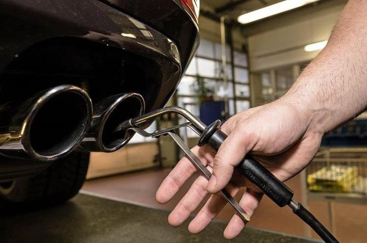 Fotografía de archivo tomada el 5 de enero de 2018 muestra a un técnico que inspecciona el tubo de escape de un vehículo en un garaje de la Asociación Alemana de Inspección Técnica en Berlín (Alemania). (Foto Prensa Libre: EFE)