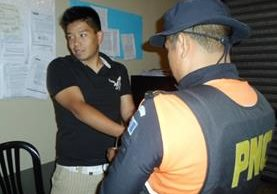 Un policía coloca las esposas en las manos de Hugo Arrecís Yang, al momento de su captura. (Foto Prensa Libre: Carlos Ventura).