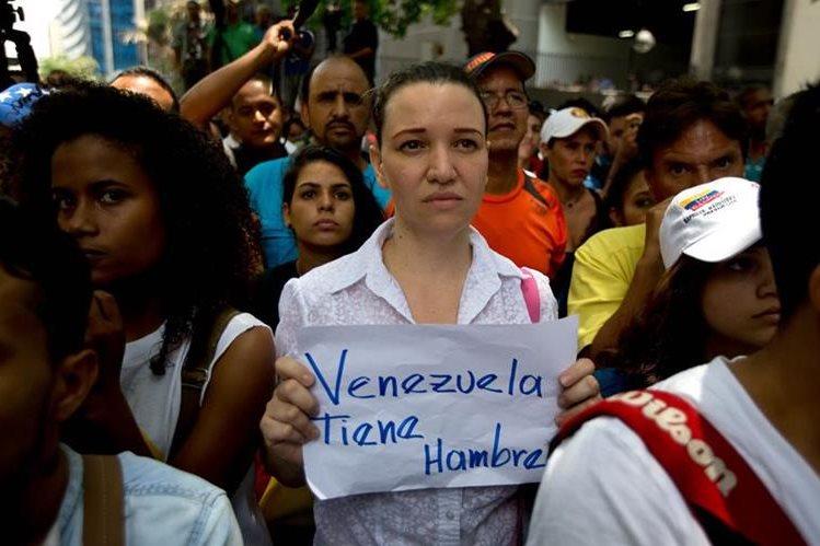 Una mujer porta una pancarta durante las recientes manifestaciones contra las políticas de Nicolás Maduro en Venezuela. (Foto Prensa Libre: AP).