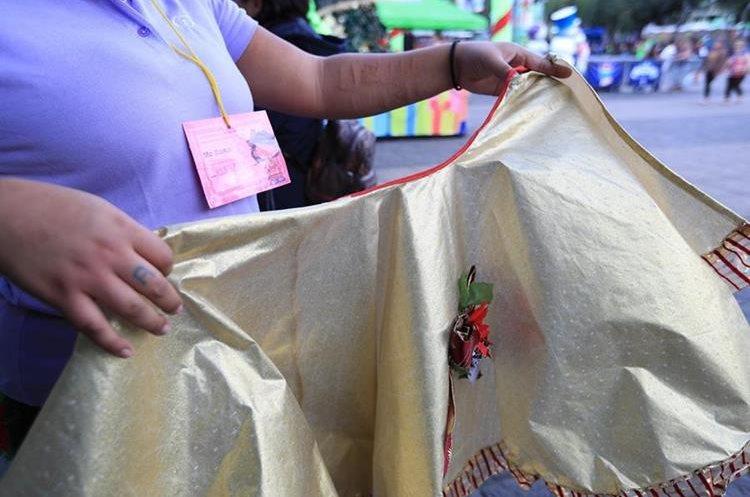 Una adolescente muestra una prenda exhibida en el bazar. (Foto Prensa Libre: Carlos Hernández).