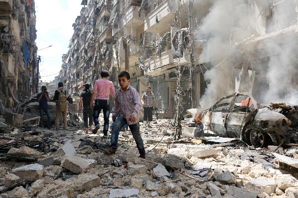 Sirios <span>caminan</span> <span>en medio de</span> <span>los escombros de</span> <span>edificios destruidos</span> por <span>un</span> <span>ataque aéreo. (AFP).</span>