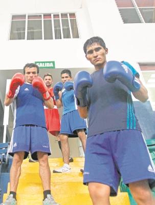 Los cuatro boxeadores nacionales posan y reflejan una mirada seria y ganadora: Juan Reyes —izquierda al frente—; Carlos Tobar —derecha al frente—: atrás, Álvaro Vargas —rojo— y Eddie Valenzuela —azul—.