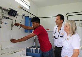 Representantes del Club Rotario observan mientras un líder de Carmelita recibe líquido purificado del sistema instalado en esa comunidad. (Foto Prensa Libre: Rigoberto Escobar)
