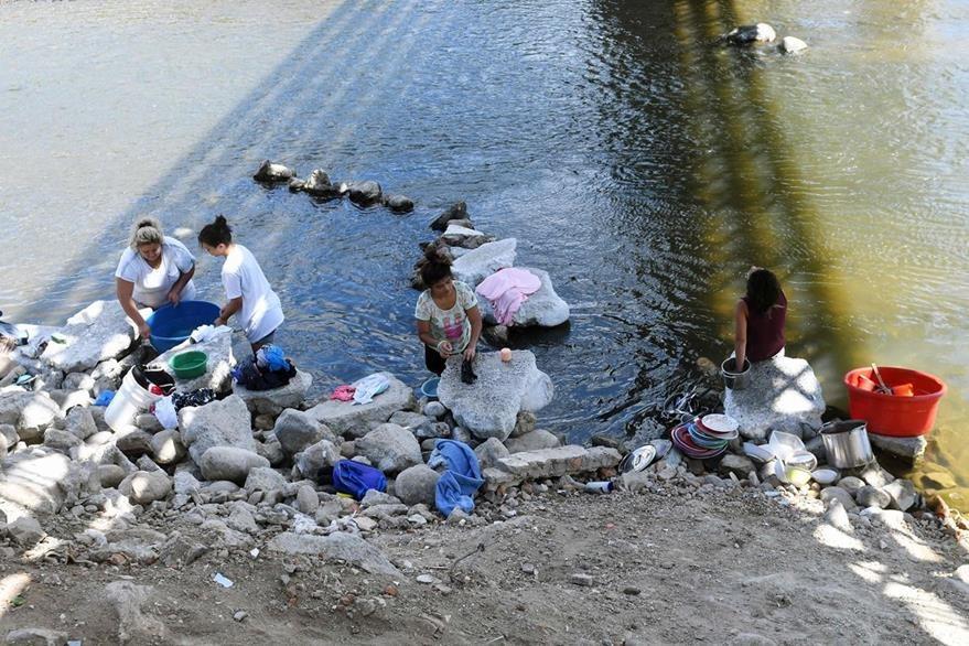 Las mujeres lavan ropa y platos en las aguas contaminadas del río Lempa en Citala, a 100 kilómetros al norte de San Salvador. (Foto Prensa Libre: AFP).