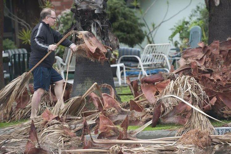Un hombre limpia el frente de su vivienda luego del fuerte viento en California. (Foto Prensa Libre: AP).