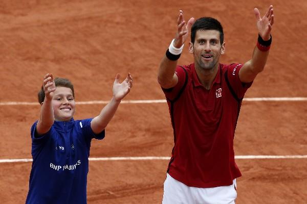 Novak Djokovic celebra con un pequeño alcanza pelotas tras superar a Roberto Bautista, de España. (Foto Prensa Libre: EFE).