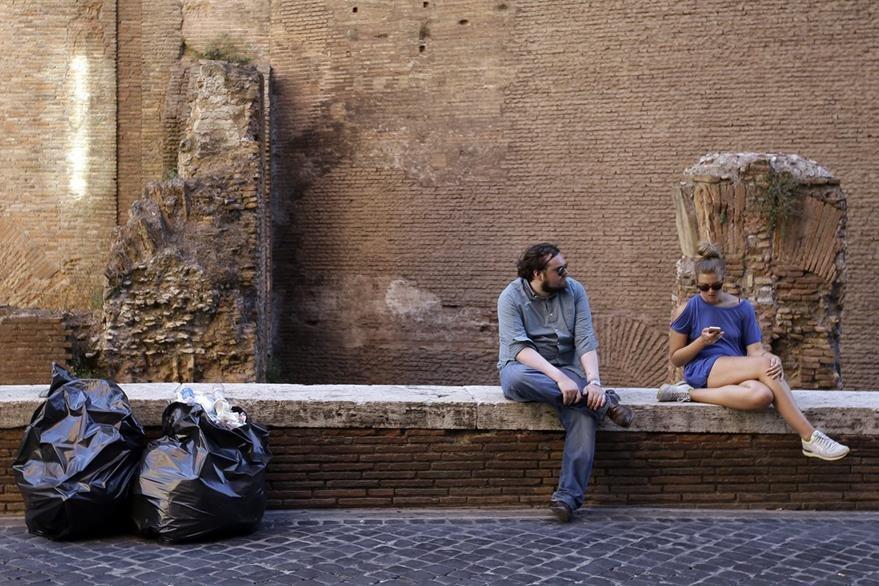Turistas conversan junto a un par de bolsas llenas de basura en Roma. (Foto Prensa Libre:AP).