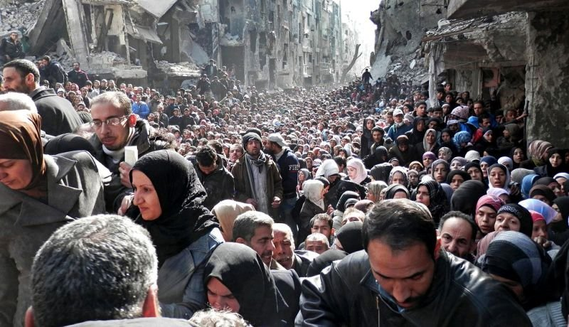 En 2014 esta fotografía dio la vuelta al mundo. Miles de refugiados sirios de Yarmuk huían de la violencia y del Estado Islámico. Los rostros desesperados de hombres y mujeres figuran en lo que parece una interminable fila humana con la ciudad que un día los albergó, en ruinas.
