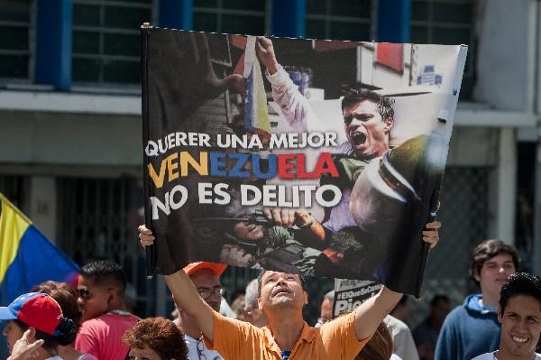Un hombre sostiene un afiche de Leopoldo López afuera del Palacio de Justicia.