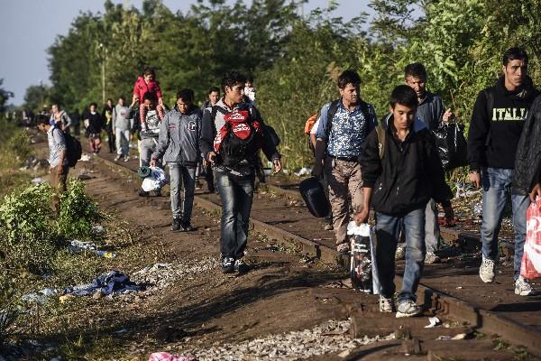 """<em><span class=""""hps"""">Refugiados</span> <span class=""""hps"""">caminar</span> <span class=""""hps"""">a lo largo de</span> <span class=""""hps"""">una vía de ferrocarril</span> <span class=""""hps"""">entre la frontera</span> <span class=""""hps"""">de Hungría</span> <span class=""""hps"""">y Serbia</span><span>.</span></em>"""