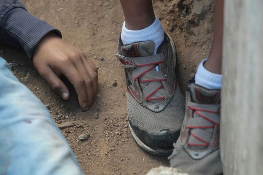 El hermano de la víctima, un niño de unos 10 años, permanece a un lado del cadáver en el patio de la vivienda. (Foto Prensa Libre: Erick Avila)