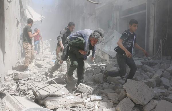 Sirios eyudan a un herido en medio de los escombros de un edificio en Alepo. (AFP).