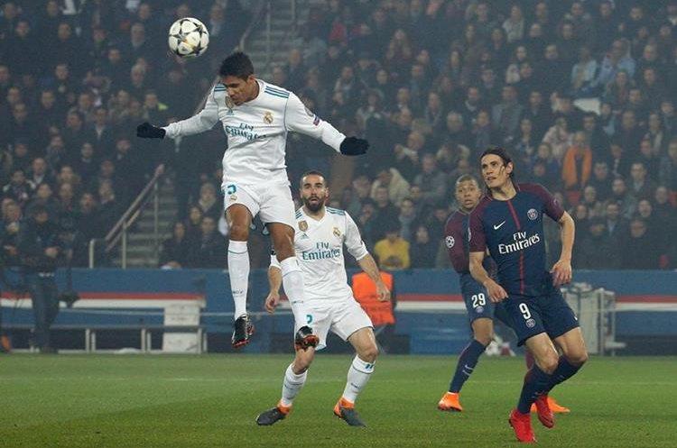 Raphael Varane salta y rechaza de cabeza un centro en el área del Real Madrid.