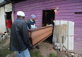 Vecinos cargan el ataúd con los restos de un piloto de autobús asesinado por pandilleros.(AFP)