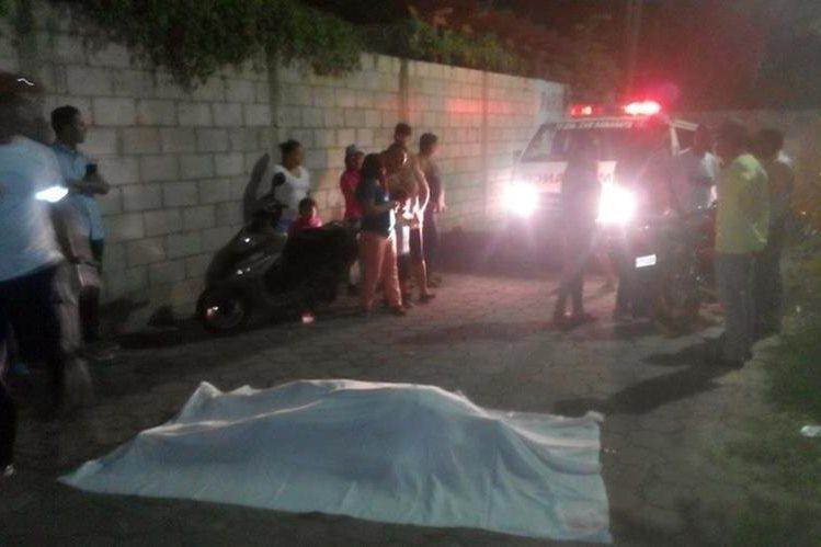 El cadáver de Manuel Humberto Valdez Pineda cubierto con una manta, ante las miradas de vecinos y socorristas. (Foto Prensa Libre: Hugo Oliva)