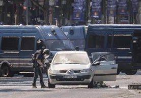 Agentes de policía galos participan en una operación en la céntrica avenida de los Campos Elíseos, donde un carro ha impactado contra un furgón de la Gendarmería francesa. (Foto Prensa Libre: EFE)
