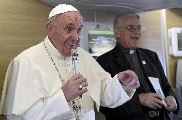 El papa Francisco (izq) se dirige a los periodistas durante el vuelo que lo trasladó desde Bangui hasta Roma.