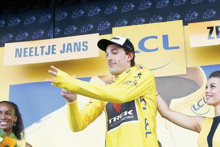 Las edecanes ayudan a Fabian Cancellara a colocarse el suéter de líder del tour. (Foto Prensa Libre: EFE)