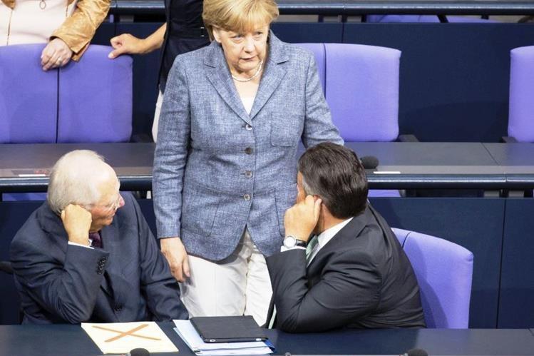 Angela Merkel conversa con los ministros de Finanzas, Wolfgang Schäuble (izq), y de Economía, Sigmar Gabriel, durante el debate y votación del tercer rescate a Grecia