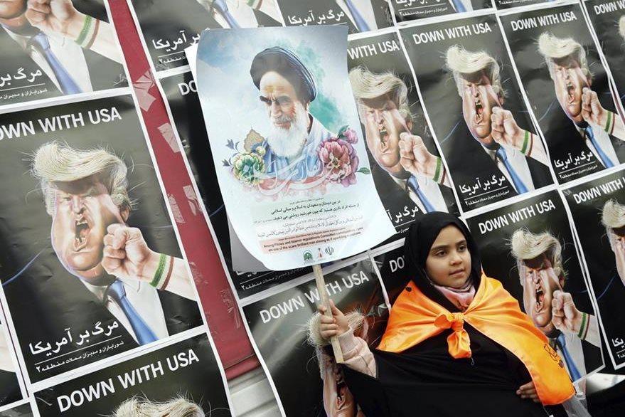 Una niña muestra un cartel del ayatolá Ruhollah Musaví Jomeini frente a pósters de Trump. (EFE).
