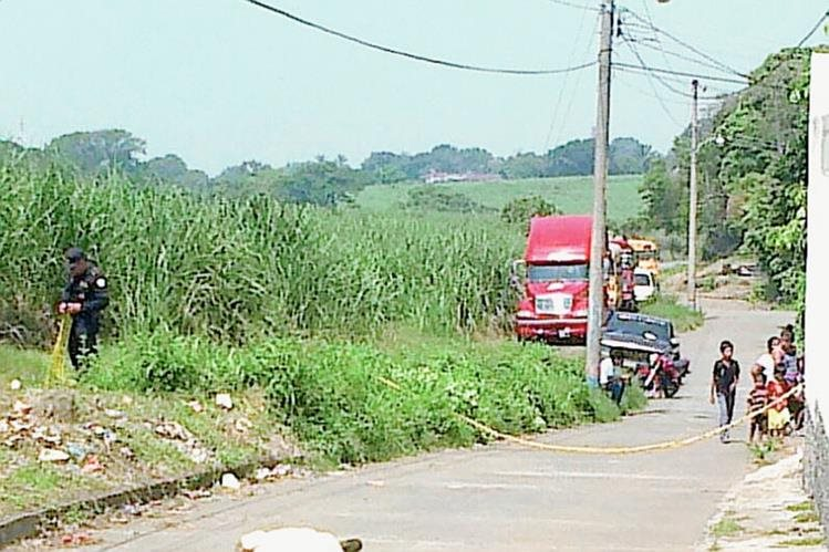 Vecinos de  la colonia Tarde Linda, en Santa Lucía Cotzumalguapa, observan cadáver de un hombre atacado a balazos. (Foto Prensa Libre: Enrique Paredes)
