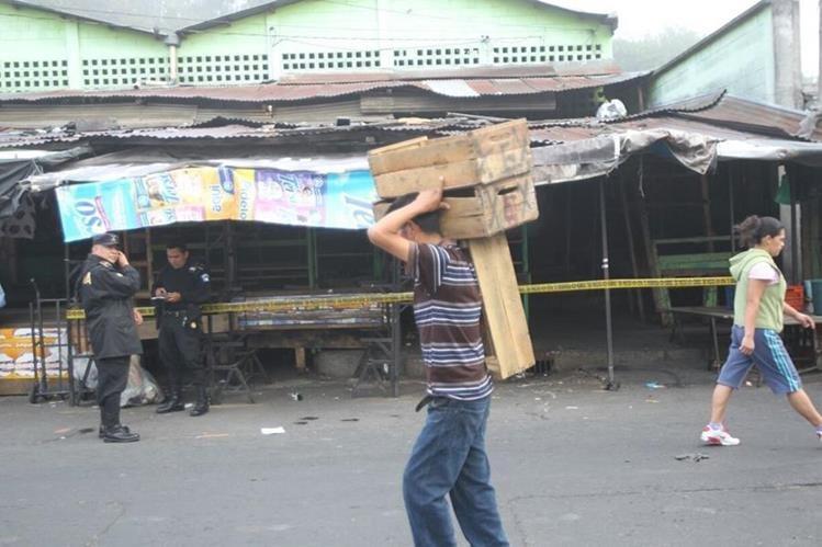 Vendedores comienzan a laborar mientras la PNC resguarda el lugar donde se localizó el cadáver. (Foto Prensa Libre: Érick Avila)