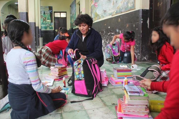 Con la participación de maestros y padres de familia, una comisión de seguridad revisa las mochilas de estudiantes. (Foto Prensa Libre: Mike Castillo)