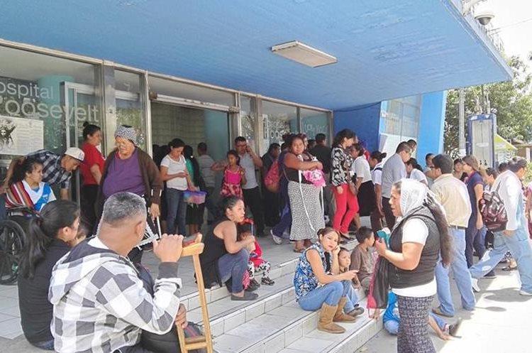 Personas esperan afuera del hospital Roosevelt la hora de la visita para ver a sus familiares que permanecen internos. (Foto Prensa Libre: Roni Pocón)