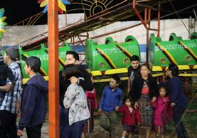 Padres de familia corren para poner a salvo a sus hijos, quienes utilizaban el juego mecánico que se descarriló. (Foto Prensa Libre: Héctor Cordero)