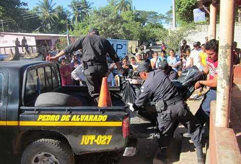 Agentes de la Policía retiran el cadáver de la tienda donde fue ultimado. (Foto Prensa Libre: Óscar González)