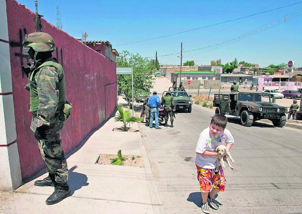 Un niño transita por una calle fuertemente custodiada en Chihuahua, estado donde han ocurrido varios crímenes contra menores. (Foto Hemeroteca PL).