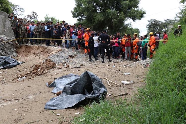 Curiosos se aglomeran en el área donde ocurrió el hallazgo y ven al cuerpo cubierto por nailon negro. (Foto Prensa Libre: Mike Castillo)