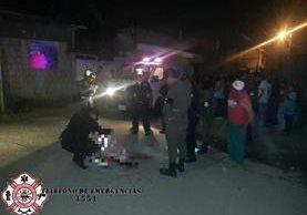 Un agente de la Policía cubre el cadáver del fallecido en la colonia San José. (Foto Prensa Libre: Asonbomd)