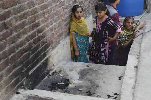 Curiosos observan el lugar donde una mujer fue quemada por su madre. (AP).