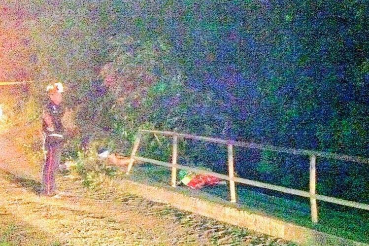 Bombero observa cadáveres baleados de mujeres en la orilla del río Pensativo, Antigua Guatemala, Sacatepéquez. (Foto Prensa Libre: Miguel López)