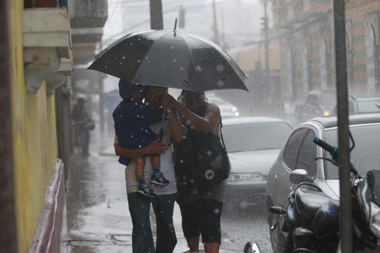 Una familia se cubre de la lluvia en una avenida de la zona 1. (Foto Prensa Libre: Hemeroteca PL)