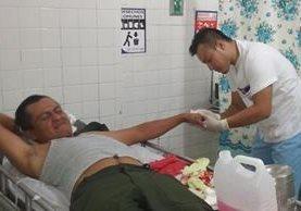 El agente de seguridad que frustró el asalto, es atendido por un para médico en la sala de urgencias del hospital de San Benito. Foto Prensa Libre: Rigoberto Escobar.