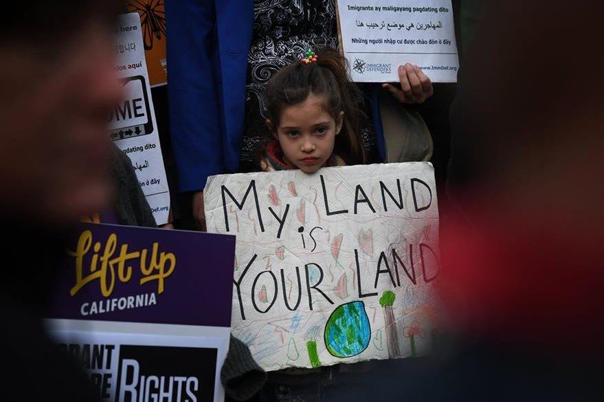 Una niña sostiene un cartel en favor de los migrantes durante una protesta en Los Ángeles. (Foto Prensa Libre: AFP)